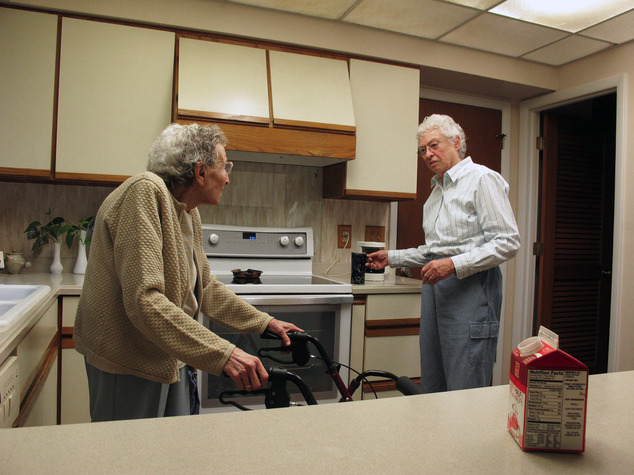 In this Friday, Aug. 1, 2014 photo, Lennie Gerber, right, hands a cup of coffee to her spouse, Pearl Berlin, in the kitchen of their High Point, N.C., home. Berlin is 89, and in fragile health, so their fight to overturn North Carolina's gay marriage ban has taken on an urgency. (AP Photo/Allen G. Breed)