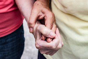 Senior Women Holding Hands Outdoors Close-up.